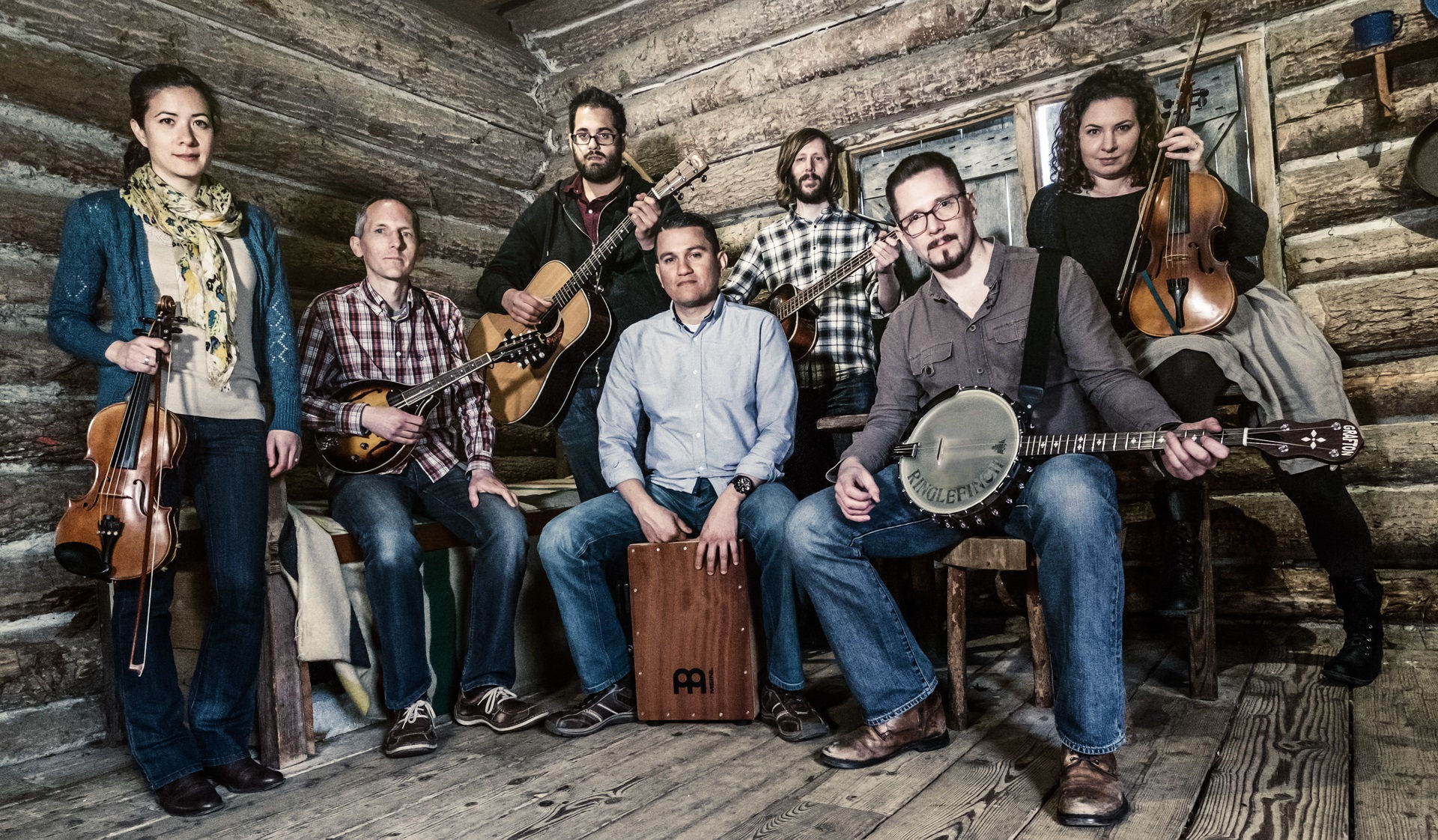 The seven members of Ringlefinch sit in a semi-circle facing the camera, in a log cabin. They hold their instruments, and look like they're just about to start playing.